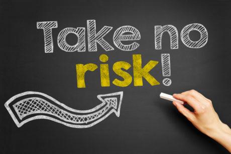"""Hand schreibt """"Take no risk!"""" auf Tafel mit Kreide"""