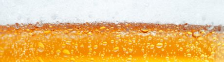 Close-up picture of a beer with the foam in the top and bubbles.