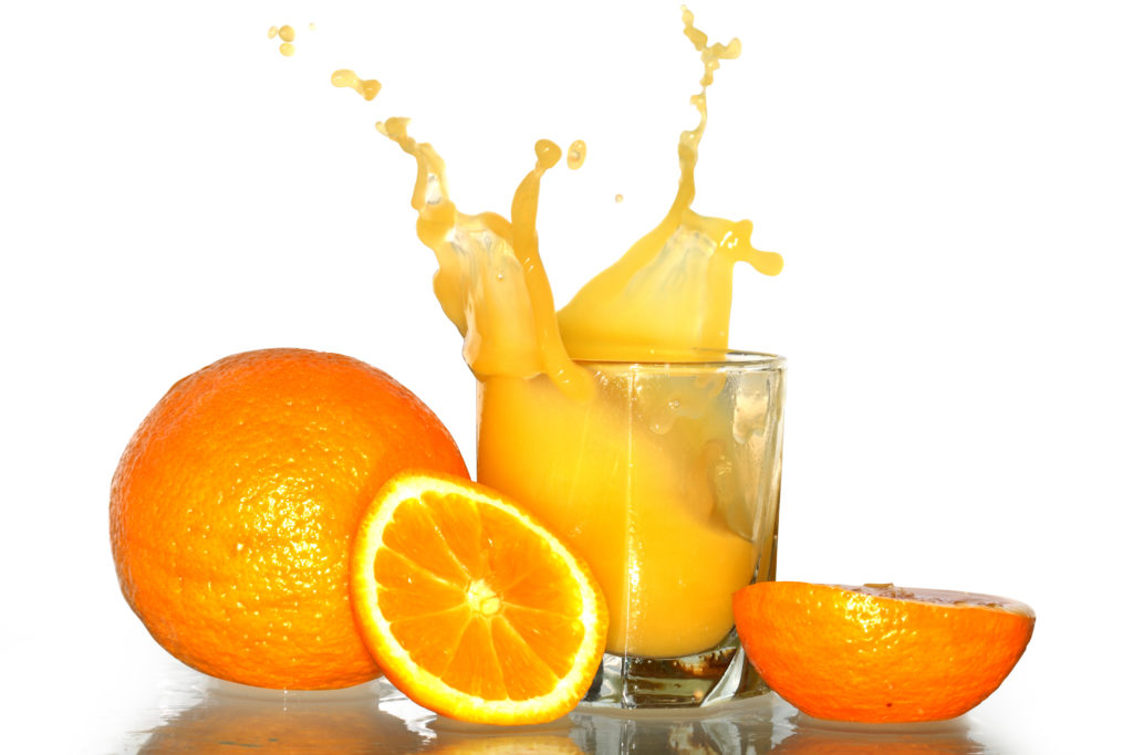Glass with splashing orange juice and oranges isolated with clipping path on white background
